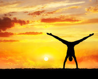 Yoga handstand silhouette. Man doing Yoga handstand on the grass at sunset sky Royalty Free Stock Photo