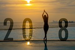 Yoga Happy new year card 2018. Silhouette woman practicing yoga on swimming pool standing as part of Number 2018 near the beach at. Sunset.  Healthy & Holiday Royalty Free Stock Image