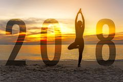 Yoga Happy new year card 2018. Silhouette woman practicing yoga standing as part of Number 2018. Near the beach at sunset.  Healthy & Holiday Concept Stock Photos