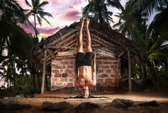 Yoga head stand without hands. Yoga niralamba shirshasana, head stand pose without hands by fit man with dreadlocks on the beach near the fishermen hut in Stock Image
