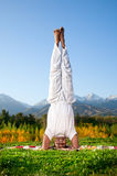 Yoga head standing. Yoga shirshasana head standing pose by happy Indian Man in white cloth in the morning at mountain background Royalty Free Stock Images