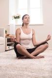 Yoga hemma. Härliga unga kvinnor som hemma mediterar  Arkivbild