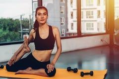 Yoga hermosa de la mujer que estira el cuerpo antes de entrenamiento del ejercicio hacia fuera fotografía de archivo