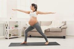 Yoga heureux de formation de femme enceinte dans la pose de héros photos libres de droits