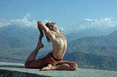 Yoga in Himalayas. Man practicing yoga in Himalaya mountains, with view of Machapuchare, Nepal Stock Photo