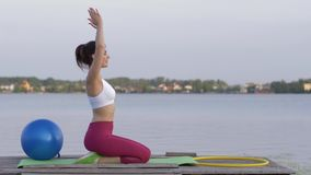 Yoga hobby, young attractive yogi female in lotus position meditates and delight spiritual calmnes near water. Yoga hobby, young attractive yogi female in lotus stock video footage