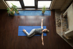 Yoga at home: Belly Twist Pose. Attractive young woman working out in living room, doing yoga exercise on wooden floor, lying in Belly Twist Pose, Jathara Royalty Free Stock Photo