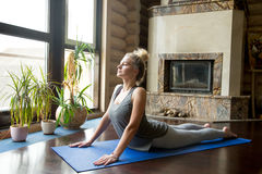 Yoga at home: Cobra Pose. Full length portrait of attractive young woman working out at home in living room, doing yoga or pilates exercise on blue mat, pose for Stock Image