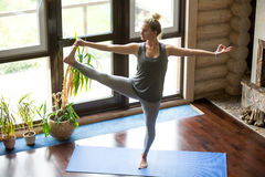 Yoga at home: Extended Hand to Big Toe pose. Full length portrait of attractive young woman working out at home in living room, doing yoga or pilates exercise on stock image
