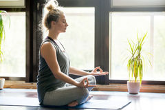 Yoga at home: meditating woman. Attractive young woman working out at home, doing yoga exercise on blue mat, sitting in Easy Decent, Pleasant Posture Royalty Free Stock Photos