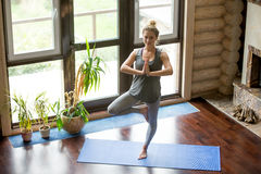 Yoga at home: Tree Pose. Full length portrait of attractive young woman working out at home in living room, doing yoga or pilates exercise on blue mat, standing Stock Image