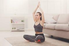 Yoga at home, woman do lotus pose royalty free stock image