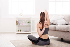 Yoga at home. Woman stretching in lotus pose royalty free stock photo