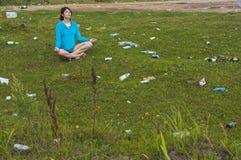 Yoga i avskräde Kvinnan öva yoga på den skräpade ner gräsmattan arkivfoton