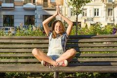 Yoga i stad, den tonårs- flickan sitter i lotusblomma poserar på bänk i stad parkerar r arkivfoton