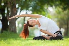 Yoga im Freien Die glückliche Frau, die Yogaübungen tut, meditieren im Park Yogameditation in der Natur Konzept des gesunden Lebe Stockfotografie