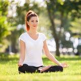 Yoga im Freien Die glückliche Frau, die Yogaübungen tut, meditieren im Park Yogameditation in der Natur Konzept des gesunden Lebe Stockbilder