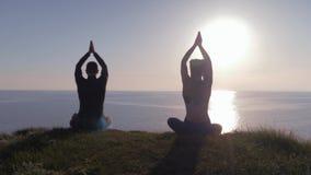 Yoga im Freien während des Sonnenuntergangs, athletisches Paar, das in Lotussitz auf Berg meditiert und das Meer, Ansicht betrach stock footage