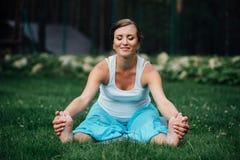 Yoga incinta nella posizione di loto sui precedenti della foresta nel parco l'erba, all'aperto, donna di salute Fotografia Stock Libera da Diritti