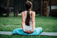 Yoga incinta nella posizione di loto sui precedenti della foresta nel parco la stuoia dell'erba, all'aperto, donna di salute Immagine Stock