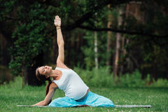 Yoga incinta nella posizione di loto sui precedenti della foresta nel parco la stuoia dell'erba, all'aperto, donna di salute Fotografie Stock