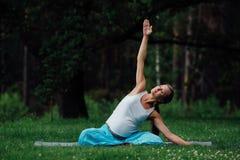 Yoga incinta nella posizione di loto sui precedenti della foresta nel parco la stuoia dell'erba, all'aperto, donna di salute Fotografia Stock