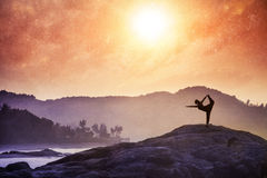 Yoga in India. Woman doing Yoga natarajasana dancer pose on the rocks at sunset at Om beach, Gokarna, India