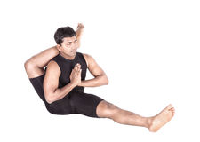 Yoga by Indian man on white. Yoga eka pada shirshasana foot behind the head pose by Indian man in black costume isolated at white background Royalty Free Stock Photo