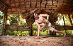 Yoga in Indian shala. Yoga Parivrtta Parsvakonasana twisting pose by fit man in white trousers on the drought earth in yoga shala, Varkala, Kerala, India Royalty Free Stock Images