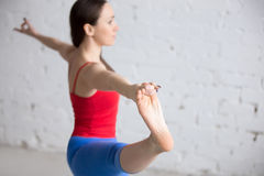 Yoga indoors: Extended Hand to Big Toe pose. Beautiful young woman in bright colorful sportswear working out indoors in loft interior. Girl standing in Utthita stock photos