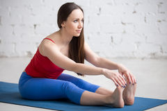 Yoga Indoors: Paschimottanasana pose. Portrait of beautiful young woman in bright colorful sportswear working out indoors in loft interior. Girl sitting in Stock Photography