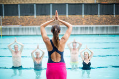 Yoga instructor assisting senior swimmers at poolside. Rear view of yoga instructor assisting senior swimmers at poolside Royalty Free Stock Photography