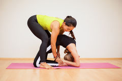 Yoga instructor assisting a student Stock Photo