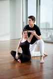 Yoga Instructor Assisting Woman Royalty Free Stock Images