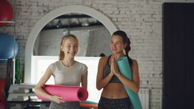 Yoga instructor is chatting with young blond student while walking togehter through studio after practice. Teacher. Attractive female yoga instructor is chatting stock video footage