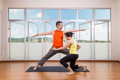 Yoga instructor correcting student performing Warrior 2 or Virab Stock Photos