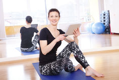 Yoga instructor with digital tablet Royalty Free Stock Photo