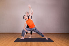 Yoga instructor guiding student perform extended side angle pose royalty free stock photography
