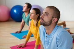 Yoga instructor guiding students in practicing cobra pose Stock Photo