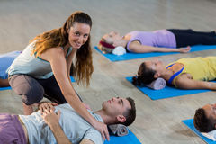 Yoga instructor helping student with a correct pose Royalty Free Stock Images