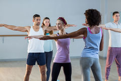 Yoga instructor helping student with a correct pose Royalty Free Stock Photo