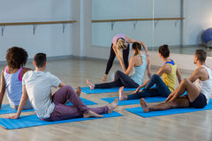 Yoga instructor helping student with a correct pose Royalty Free Stock Photography