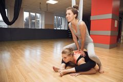 Yoga instructor helps beginner to make stretching exercises in t royalty free stock images