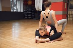 Yoga instructor helps beginner to make stretching exercises. In the studio Stock Photos