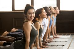 Yoga instructor looking at camera doing exercise at group traini. Smiling yoga instructor looking at camera doing fitness stretching backbend exercise together stock image