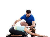 Yoga instructor positioning woman adho mukha virasana child pose. Adho mukha virasana child pose yoga stretching workout posture by a couple, a men  instructor Royalty Free Stock Photography