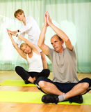 Yoga instructor showing asana to mature couple Stock Photos