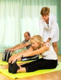 Yoga instructor showing asana to mature couple Royalty Free Stock Image