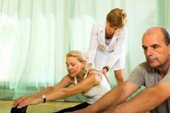 Yoga instructor showing asana to mature couple Stock Image