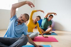 Yoga instructor with students exercising at club. Yoga instructor with students exercising at health club Royalty Free Stock Photos